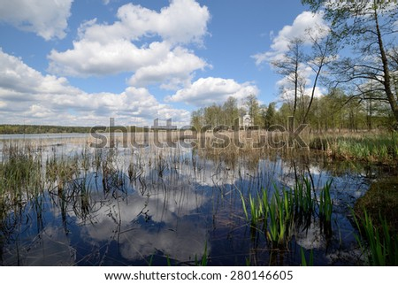 Reflexion of clouds in the spring lake - stock photo