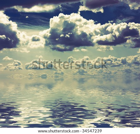 Reflexion of the cloudy sky in the sea - stock photo