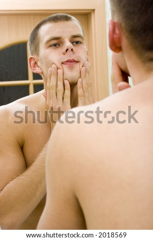 reflexion of young man in the bathroom's mirror after shave - stock photo