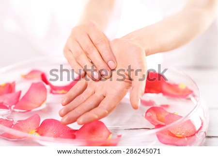 Reflexology, a gentle hand massage . Beauty ritual for hands. Care treatment of hands and nails woman hands over the bowl with rose petals  - stock photo