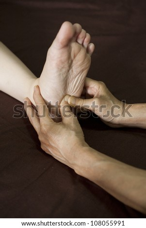 reflexology foot massage, spa foot treatment. - stock photo
