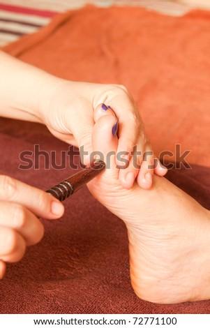 reflexology foot massage, spa foot treatment by wood stick,Thailand - stock photo