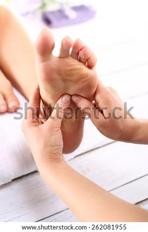 Reflexology.Masseuse massaging woman's foot. - stock photo