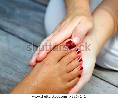 Reflexology woman feet massage therapy outdoor - stock photo