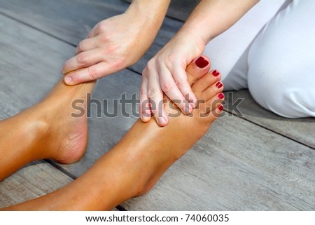Reflexology woman feet massage therapy outdoor - stock photo