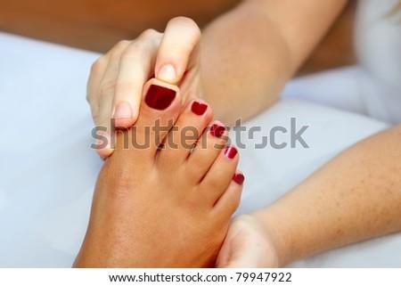 Reflexology woman feet massage therapy red fingernails - stock photo