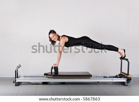 Reformer front support position. Pilates gymnastics is a Germanic evolution of yoga, used by athletes to improve flexibility and body fitness and by chiropractors for patient recovery. - stock photo