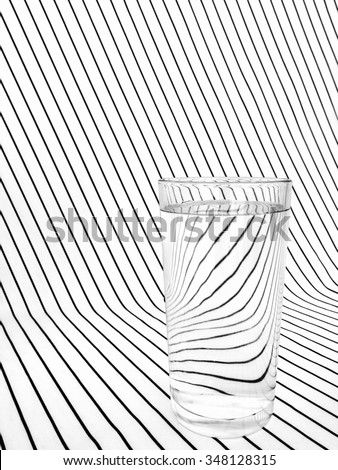 Refraction effect with one tumbler, glass of water on striped fabric. Distorted lines due to light bending. - stock photo