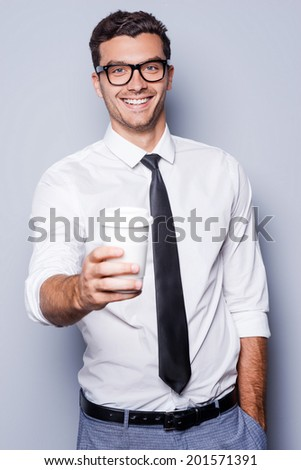 Refresh your mind! Confident young man in shirt and tie stretching out coffee cup and smiling while standing against grey background - stock photo