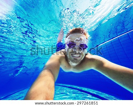 Refreshing at pool. Underwater wide angle selfie shot. - stock photo