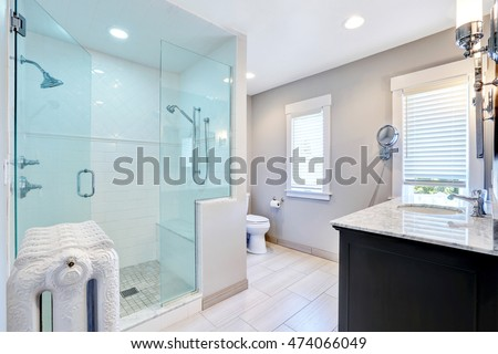 Refreshing bathroom with large glass walk in shower with two heads and cast-iron radiator in retro style. Northwest, USA
