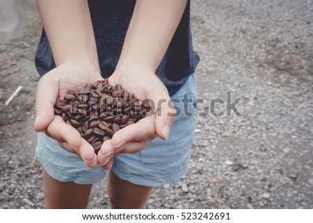 Refreshing beans. Close up of young asian woman holding some coffee beans in her hands.