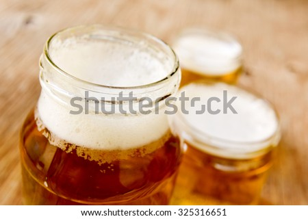 refreshing beer served in glass jars on a rustic wooden surface - stock photo