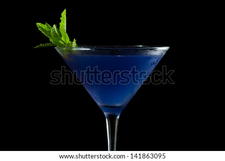 refreshing blue martini served isolated on a black background garnished with fresh mint - stock photo