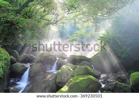 Refreshing cascades in a mysterious forest with sunbeams shining through lavish greenery ~ Beautiful river scenery of Taiwan in springtime - stock photo