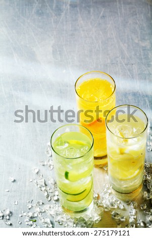 Refreshing chilled tropical fruit cocktails with sliced lemon, lime and orange served in long glasses with crushed ice and copyspace - stock photo