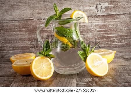 refreshing citrus lemonade,summer drink. Lemonade with fresh lemon on wooden background - stock photo