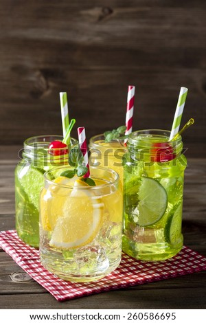 Refreshing cocktails in mason jars over wooden background - stock photo