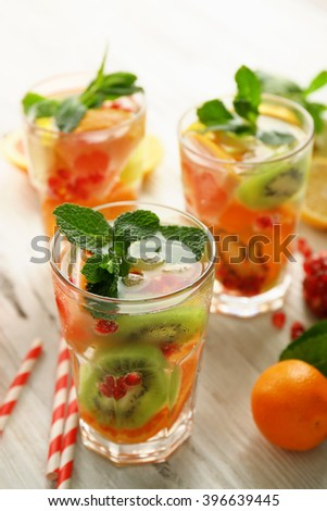 Refreshing cocktails with ice, mint, pomegranate seeds and slices of fruits on light wooden background