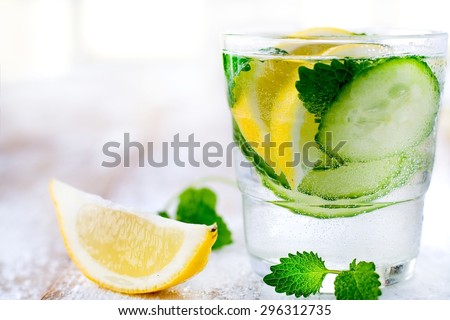 Refreshing drink: home-made flavored water with lemon, cucumber, fresh lemon balm. Fresh and fruity. - stock photo