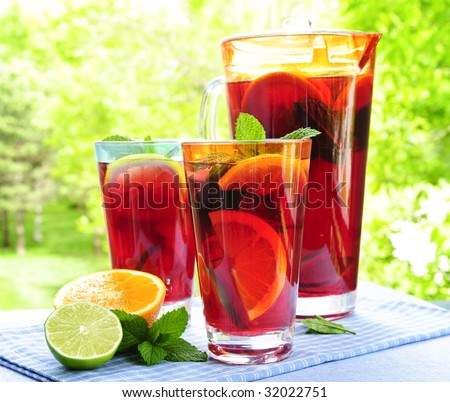 Refreshing fruit punch beverage in pitcher and glasses - stock photo