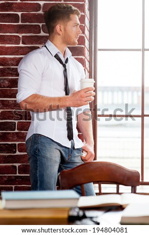 Refreshing his mind. Handsome young man in shirt and tie holding coffee cup and looking through the window while sitting at the window sill  - stock photo