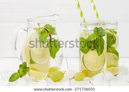 Refreshing homemade lime and mint cocktail over old vintage wooden table. Detox fruit infused flavored water. Clean eating.  - stock photo