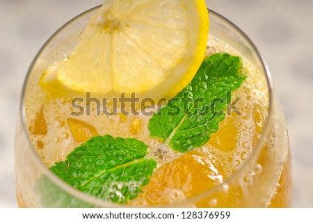 refreshing Ice tea closeup macro with lemon and mint leaves - stock photo