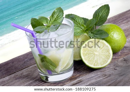 Refreshing iced rum, lime and mint mojito cocktail on an old wooden board on the golden,  tropical beach background - stock photo