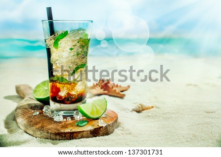Refreshing iced rum, lime and mint mojito cocktail standing in a tall glass on an old wooden board on the golden sand of an idyllic tropical beach to celebrate a summer vacation - stock photo