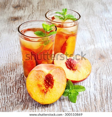 Refreshing iced tea with ripe peaches on rustic background, selective focus, square image
