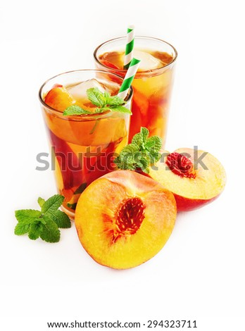 Refreshing iced tea with ripe peaches on white background, selective focus
