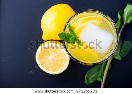 Refreshing lemonade with fresh citrus , mint and ice in glass on black background - stock photo