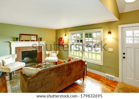 Refreshing living room with light green walls, hardwood floor and white ceiling. Furnished with brown sofa, white chairs and glass coffee table. View of the room from staircase - stock photo