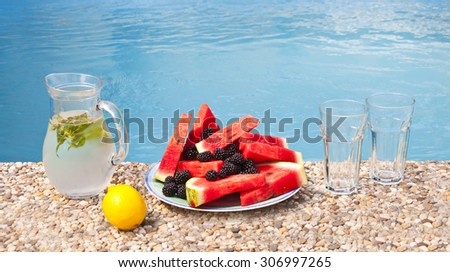 Refreshing melon plate with blackberries and cold lemonade - stock photo