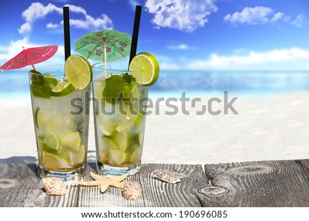 Refreshing Mojito Cocktail on Wooden Boards with Starfish and Sea Shell on the Beach with much Copy Space for additional information