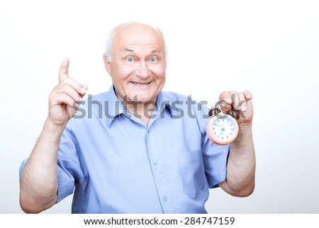 Refreshing morning. Brisk grandfather  holding the alarm clock and pointing his index finger up while expressing joy. - stock photo