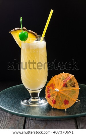 Refreshing pineapple cocktail with coconut in glass with slices of pineapple, green cocktail cherry, straws and decoration for glasses in the form of a umbrella - stock photo