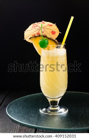 Refreshing pineapple cocktail with coconut in glass with slices of pineapple, green cocktail cherry, straws and decoration for glasses in the form of a umbrella