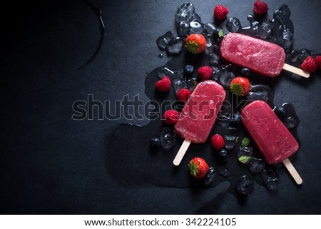 Refreshing popsicle on ice cubes and fruits, food background - stock photo