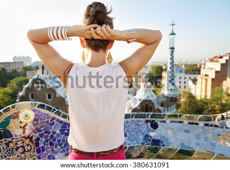 Refreshing promenade in unique Park Guell style in Barcelona, Spain. Seen from behind relaxed young woman tourist sightseeing in Park Guell, Barcelona, Spain - stock photo