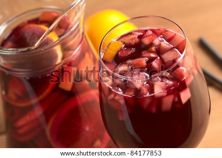 Refreshing red wine punch called sangria mixed with orange, apple, mango pieces served in wine glass (Selective Focus, Focus on the fruit pieces in the middle of the glass) - stock photo