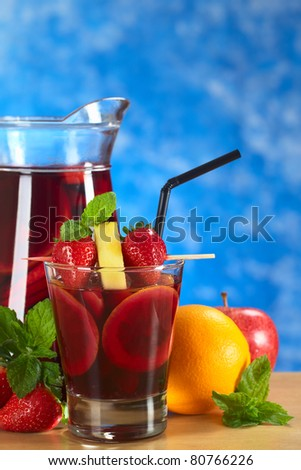 Refreshing sangria mixed with orange, apple and mango, garnished with strawberries and pineapple on skewer with a jug of sangria and fruits in the back (Selective Focus, Focus on the fruits on skewer) - stock photo