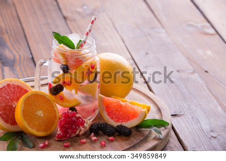 Refreshing sangria / punch with orange, pomegranate seeds, blackberry, and grapefruit on brown rustic wooden background - stock photo