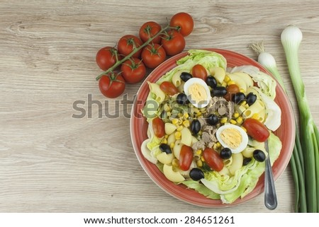 Refreshing summer dish, pasta with tuna, vegetables, olives and egg. Healthy food for athletes. - stock photo