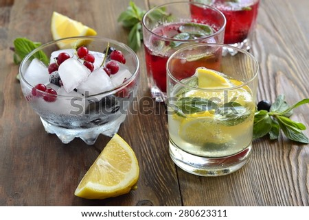 Refreshing summer drink with berries and lemon in a glass on a wooden table - stock photo