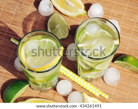 Refreshing summer drink with lemon, lime, mint and ice in glasses