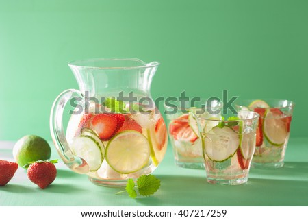 refreshing summer drink with strawberry cucumber lime in jar and glasses - stock photo