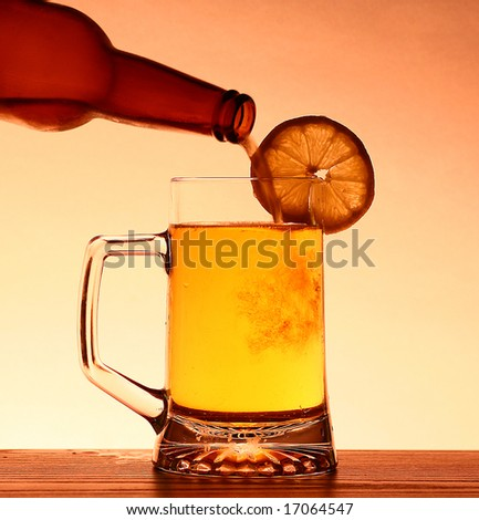 Refreshing Summer pint of beer being poured with lemon - stock photo