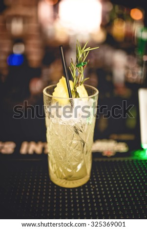 refreshment alcoholic cocktail drink at local bar. Gin and lime cocktail with rosemary and ice served cold by bartender - stock photo